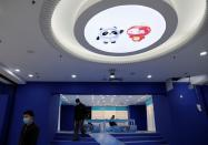 Workers walk under a light with an image of 2022 Winter Olympic Games mascots Bing Dwen Dwen and Shuey Rhon Rhon, at a souvenir shop under renovation in Beijing