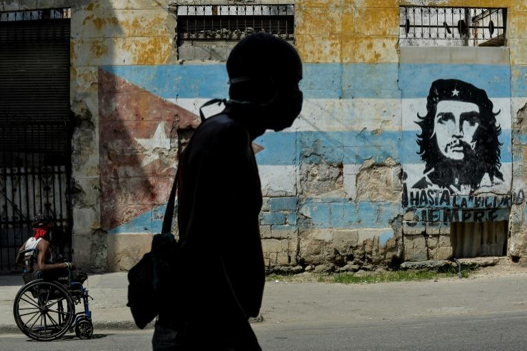 A Cuban man wears a face mask in front of a mural showing revolutionary Che Guevara in Havana -- the coronavirus cases are limited here, but food shortages have become worse as a result of the crisis (AFP Photo/YAMIL LAGE)