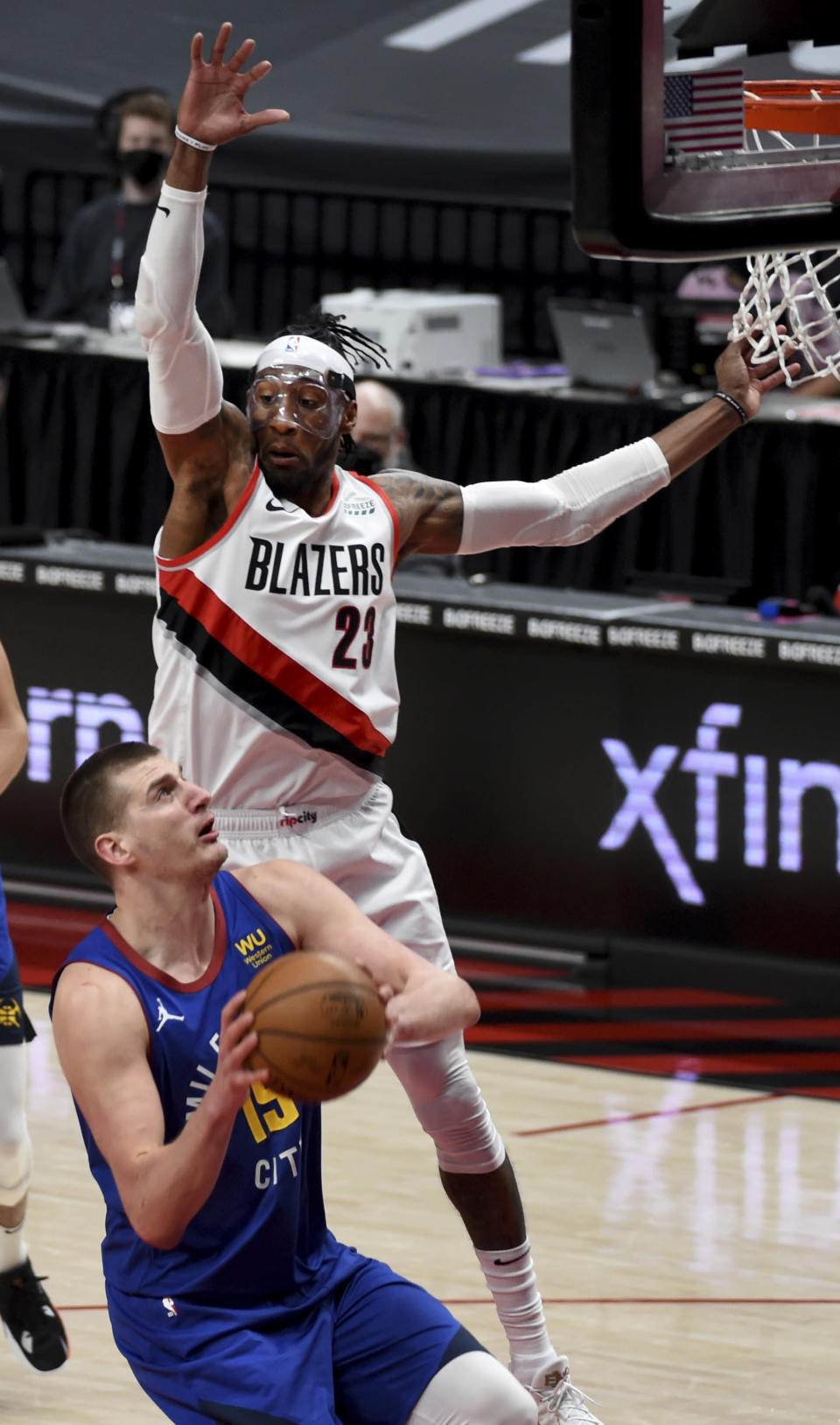 Denver Nuggets center Nikola Jokic is defended by Portland Trail Blazers forward Robert Covington during the first half of an NBA basketball game in Portland, Ore., Wednesday, April 21, 2021. (AP Photo/Steve Dykes)
