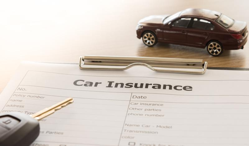 A car insurance form attached to a clipboard with a car key on top and a toy car next to the form