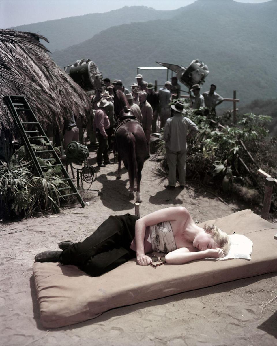 <p>Film star Grace Kelly sneaks in a nap in the African sun between takes on the set of <em>Mogambo</em>. </p>
