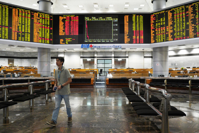 An Investor walks in front of private stock trading boards at a private stock market gallery in Kuala Lumpur, Malaysia, Friday, Nov. 23, 2018. Asian markets are mostly lower as traders dwelled on risks from a drawn-out dispute between the U.S. and China and other events closer to home. (AP Photo/Yam G-Jun)
