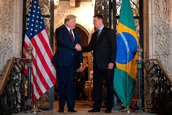 US President Donald Trump (L) shakes hands with Brazilian President Jair Bolsonaro during a diner at Mar-a-Lago in Palm Beach, FloridaAFP via Getty Images