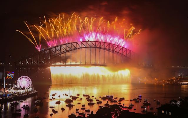 <p>Fireworks explode from the Sydney Harbour Bridge and the Sydney Opera House during the midnight fireworks display on New Year's Eve on New Year's Eve on January 1, 2018 in Sydney, Australia. (Photo: Scott Barbour/Getty Images) </p>