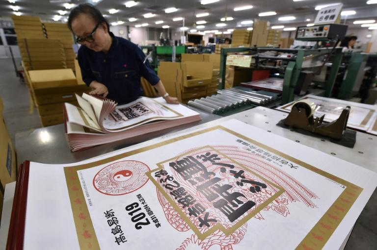 A Japanese printer checks 2019 calendars, which display the current era, known as Heisei, marking the reign of Emperor Akihito, who is expected to abdicate in May next year