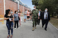 Portugal Vaccine Success - Rear Admiral Henrique Gouveia e Melo, center, talks to people queuing outside a vaccination center in Lisbon, Saturday, Sept. 11, 2021. As Portugal nears its goal of fully vaccinating 85% of the population against COVID-19 in nine months, other countries want to know how it was able to accomplish the feat. A lot of the credit is going to Gouveia e Melo. (AP Photo/Armando Franca)