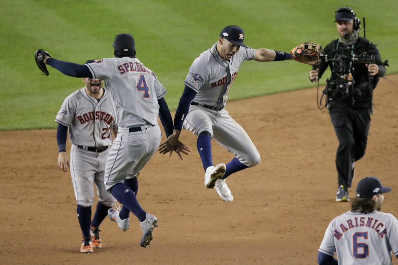 Houston Astros center fielder George Springer (4) and shortstop Carlos Correa (1) celebrate after the Astros beat the New York Yankees 8-3 in Game 4 of baseball's American League Championship Series, Friday, Oct. 18, 2019, in New York. (AP Photo/Seth Wenig)