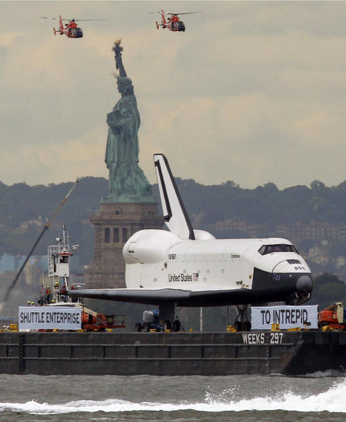 The space shuttle Enterprise, a prototype which never flew in space, travels up the Hudson River by barge to it's new home aboard the Intrepid Sea, Air and Space Museum Wednesday, June 6, 2012 in New York. The U.S. space agency, NASA, ended its shuttle program last year. (AP Photo/Kathy Willens)