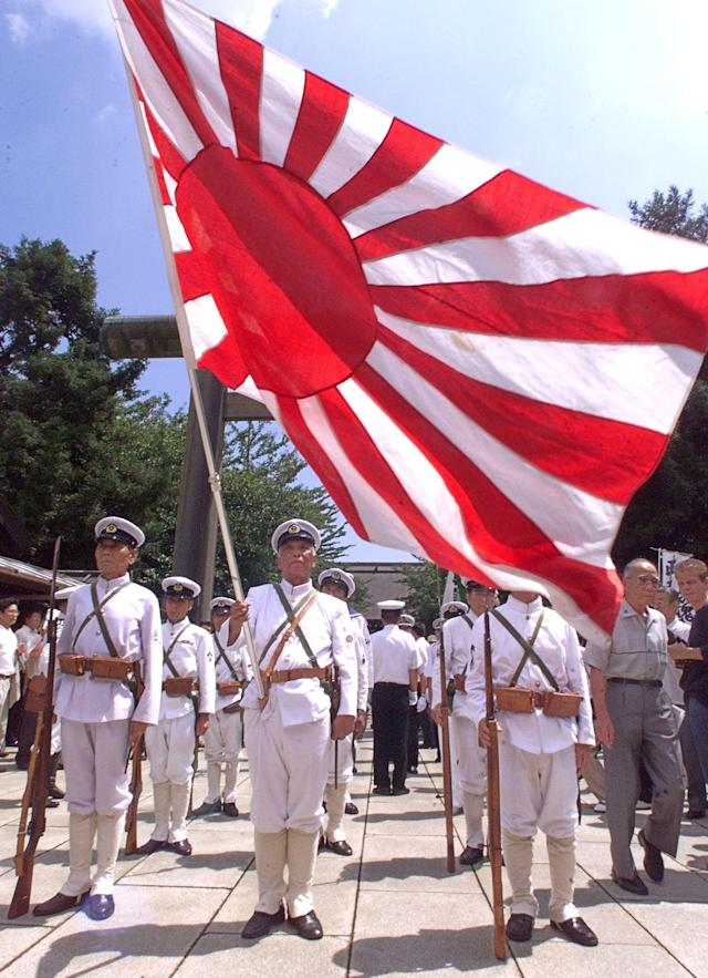 In front of the flag of the Rising Sun, World War II veterans in Imperial Navy uniforms pray for the war-dead at the Yasukuni Shrine in Tokyo 15 August 1999, on the 54th anniversary of Japan's surrender. (Toru Yamanaka/AFP via Getty Images)