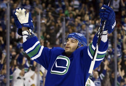Vancouver Canucks' Christopher Higgins, left, celebrates after scoring a goal against the Dallas Stars during the first period of an NHL hockey game, Friday, March 30, 2012, in Vancouver, British Columbia. (AP Photo/The Canadian Press, Darryl Dyck)
