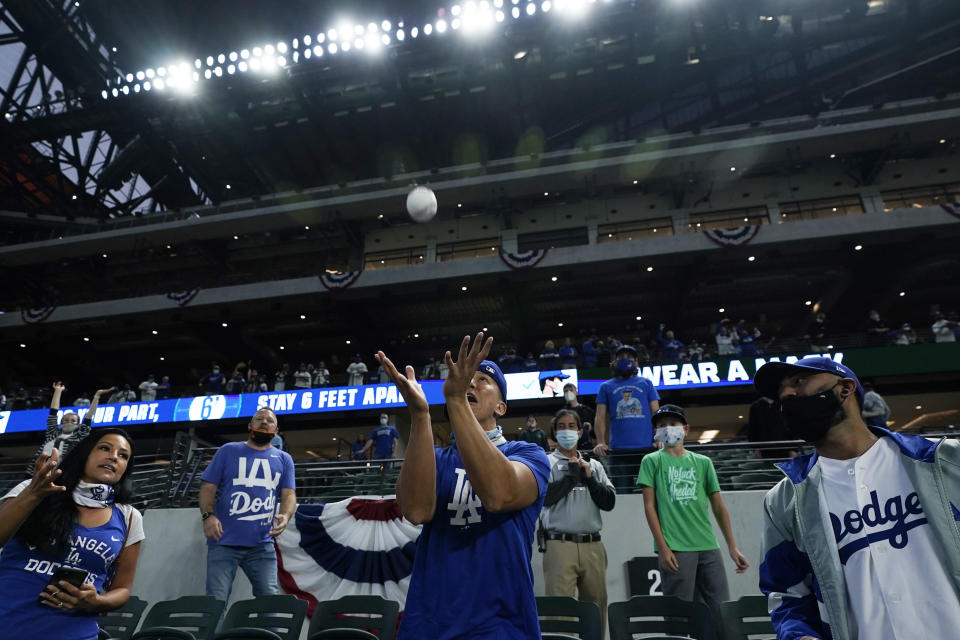 Los Angeles Dodgers fans try to catch a ball during batting practice before Game 5 of the baseball World Series against the Tampa Bay Rays Sunday, Oct. 25, 2020, in Arlington, Texas. (AP Photo/Eric Gay)