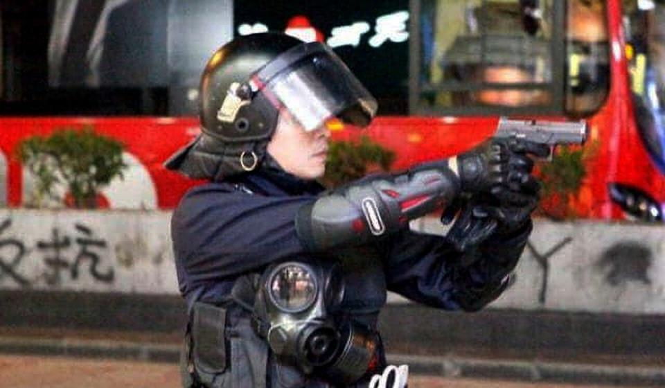 An anti-riot police officer holds up a gun during clashes with anti-government protesters in Yau Ma Tei. Photo: Handout