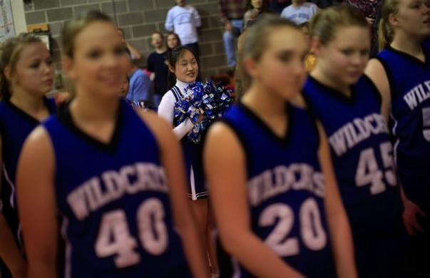 Amy Wang (REAR), a foreign exchange student from Shenyang, China, cheers during the introduction of the Grant-Deuel School Girls' Varsity basketball team before a game in Waverly, South Dakota February 14, 2012.