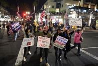 Demonstrators march across Pacific Coast Highway while shouting slogans Saturday, Nov. 21, 2020 during a protest against a stay-at-home order amid the COVID-19 pandemic in Huntington Beach, Calif. California health officials are restricting overnight activities starting Saturday night, though there are plenty of exceptions. They're calling it a limited stay-at-home order designed to stem the rapidly spreading coronavirus by discouraging social gatherings. (AP Photo/Marcio Jose Sanchez)