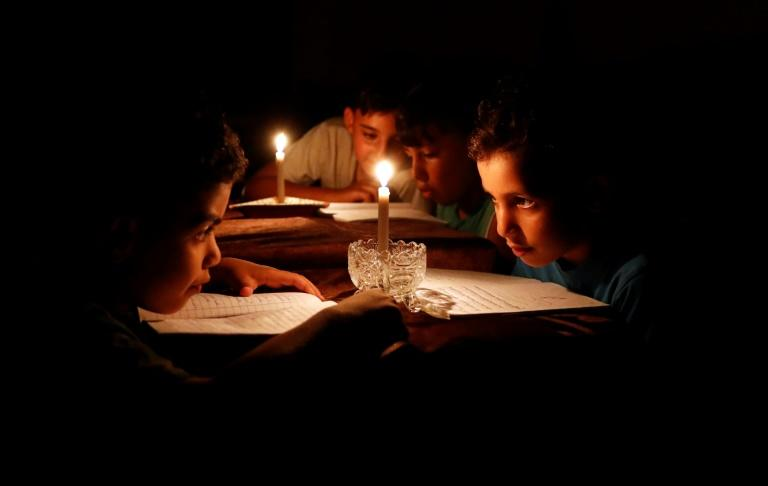 A picture taken on June 13, 2017 shows Palestinian children at home reading books by candle light due to electricity shortages in Gaza City