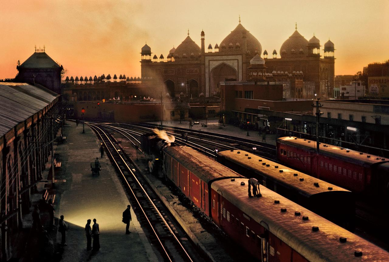 "<p>Agra Fort Railway Station at dusk, with the Jama Masjid in the distance, Agra, Uttar Pradesh, India, 1983. ""€œI photographed this image at Agra Fort Railway Station, in India, where an attendant adjusted a ventilator on the top of a train carriage. The domes and minarets of the Jama Masjid, a mosque completed in 1656 under Mughal emperor Shah Jahan, were visible in the late afternoon light."" (© Steve McCurry/Magnum Photos) </p>"