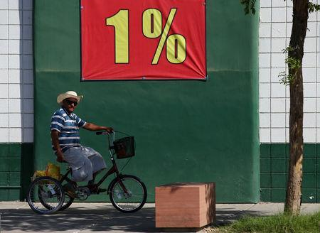 A man rides a tricycle past a grocery store in a town that borders Mexico, in San Luis Butter, California, United States, October 8, 2016. REUTERS/Mike Blake