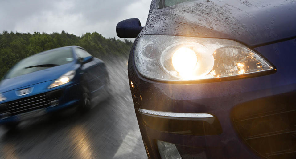 Two cars driving with headlights on. Source: Getty Images