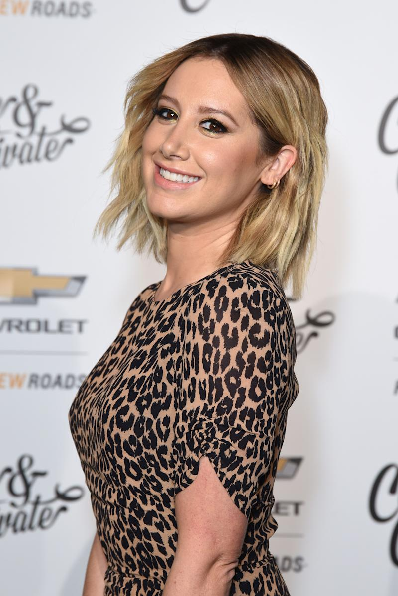 Ashley Tisdale poses smiling wearing a leopard print dress