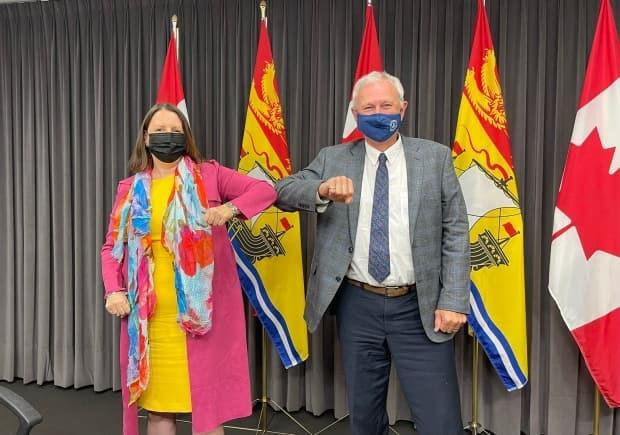 Blaine Higgs and Dr. Jennifer Russell pose for a celebratory picture taken by Higgs' chief of staff Louis Leger following an announcement July 23 that New Brunswick would be lifting COVID-19 restrictions earlier than planned. (Twitter.com - image credit)
