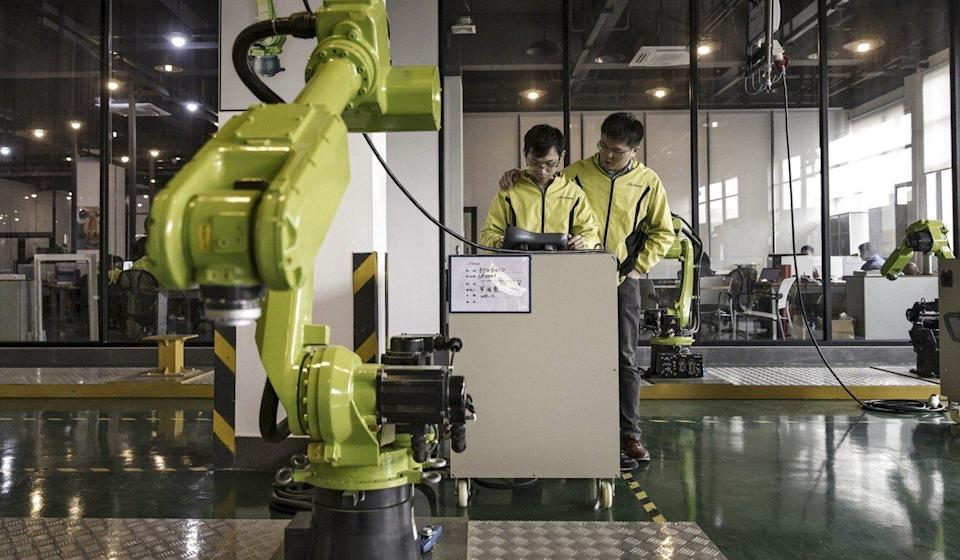 Technicians work on the testing line of a factory in Foshan, China. Photo: Bloomberg