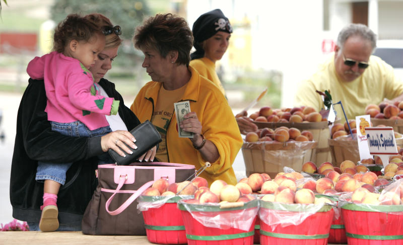 FILE - In the Sept. 1, 2006, file photo, Ally Henson, 1, and her mother Nicole Henson, 33, left, are helped by Debbie Lang, as they and other customers buy peaches at the Romeo, Mich., farm market. Farmers, growers and operators of open-air markets are heading into a busy time of the year, in early May 2020, as many states still are under stay-at-home orders for residents and non-essential businesses to slow the spread of the new coronavirus. Shoppers venturing out are just as likely to come across tables of hand sanitizer and face mask-wearing produce peddlers as they are to see bushels of corn, quarts of blueberries or flats of petunias. (Todd McInturf/Detroit News via AP, File)