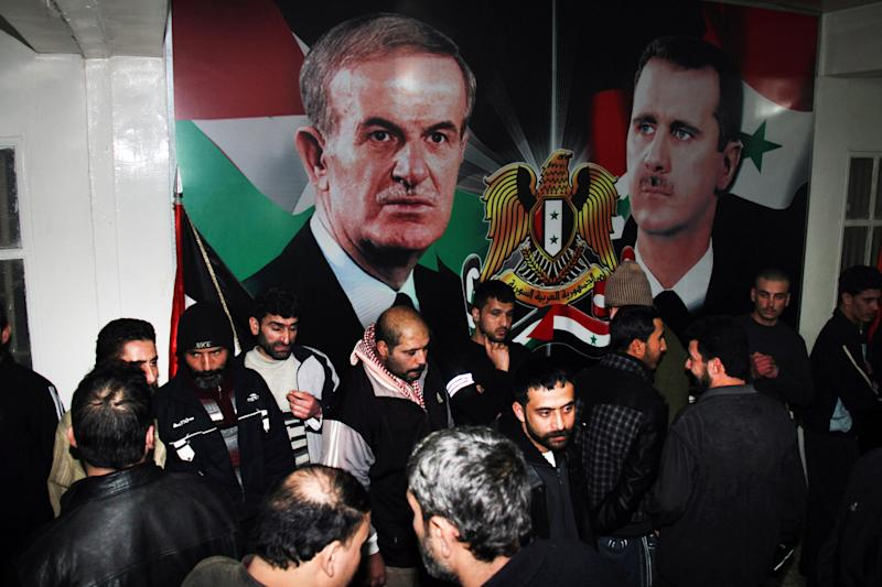 FILE - In this January 15, 2013 file photo, freed Syrian detainees gather in front of posters showing Syrian President Bashar Assad, right, and his father Hafez Assad, left, after they were released from Adra Prison on the north-east outskirts of Damascus, Syria. Syrian activists said Thursday a prominent rights lawyer believed to be in government custody for more than eight months is suffering from deteriorating health and called for his immediate release. (AP Photo/Bassem Tellawi, File)
