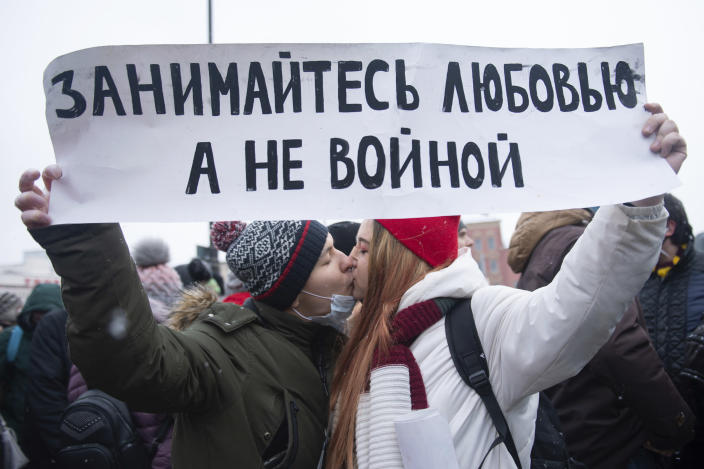 """Young demonstrators kiss and hold a banner that reads: """"Make love, Not war"""", during a protest against the jailing of opposition leader Alexei Navalny in Moscow, Russia, on Sunday, Jan. 31, 2021. Tens of thousands of people are protesting across Russia to demand the release of jailed opposition leader Alexei Navalny in wave of nationwide demonstrations that have rattled the Kremlin. Many chanted slogans against President Vladimir Putin. Activists say police detained more than 3,300 protesters across the country on Sunday, including over 900 in Moscow. (AP Photo/Denis Kaminev)"""