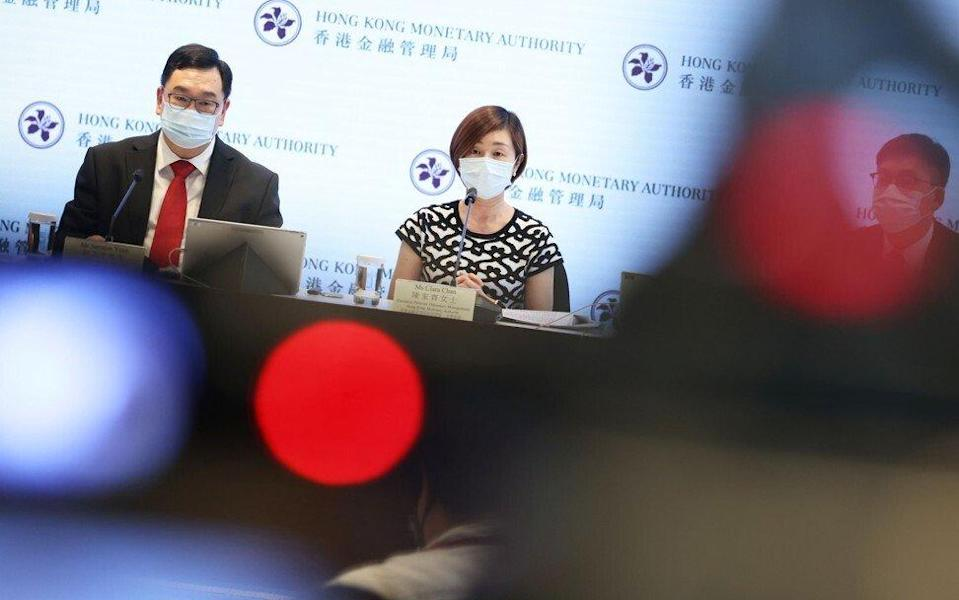 Samson Yuen, head of currency and settlement at the Hong Kong Monetary Authority, and Clara Chan, the HKMA's executive director for monetary management, speak at a June briefing on the latest round of Silver Bonds. Photo: K. Y. Cheng