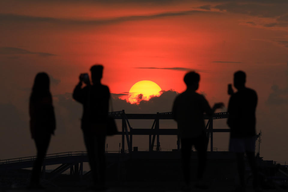 People take pictures of the sunrise on June 7, 2021 in Singapore. Singapore enters a month long heightened alert from May 16 to June 13 to curb the spread of COVID-19 cases in the local community. New restrictions on movements and activities have been introduced such as limiting social interaction to two, prohibiting dining out and a reduced operating capacity at shopping malls, offices and attractions. (Photo by Suhaimi Abdullah/NurPhoto via Getty Images)