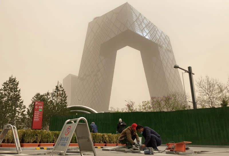 Construction workers are seen in front of the CCTV headquarters shrouded in dust as the city is hit by a sandstorm, in Beijing