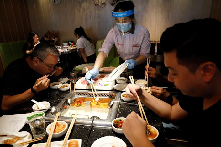 """People eat at a busy steamboat restaurant in Singapore on June 19, 2020. <p class=""""copyright"""">REUTERS/Edgar Su</p>"""
