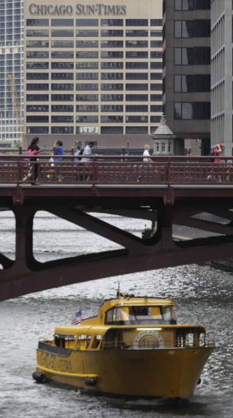 People walk on a bridge in front of The Chicago Sun Times building Thursday, May 30, 2013, in Chicago. The Sun-Times Media announced today that they laid off their entire full time photography staff at the city's tabloid newspaper, and its suburban sister publications. The union representing laid-off photographers at the Chicago Sun-Times plans to file a bad-faith bargaining charge with the National Labor Relations Board. (AP Photo/M. Spencer Green)