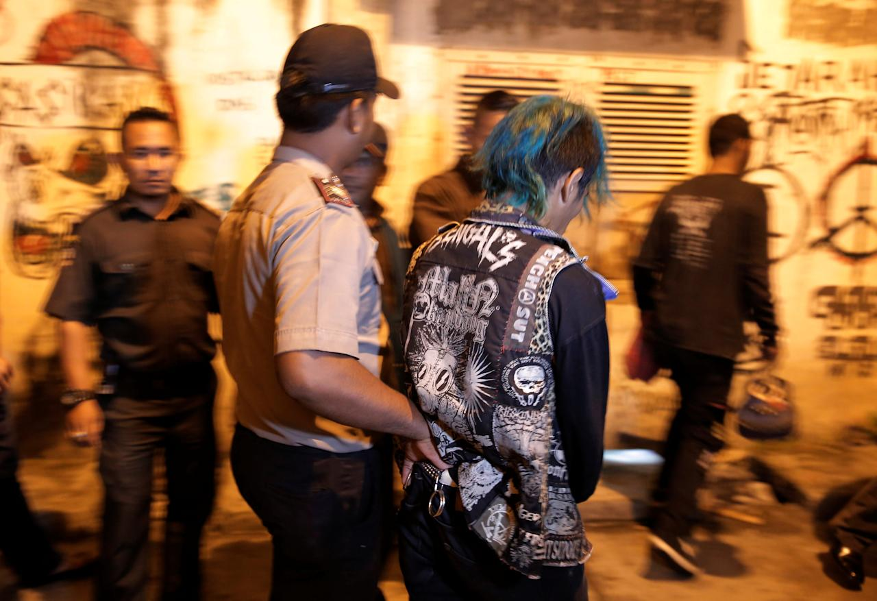 An Indonesian policeman detains a man while on patrol together with Sharia police in preparation for Ramadan, in Banda Aceh, Indonesia's Aceh province May 23, 2017. Picture taken May 23, 2017. REUTERS/Beawiharta