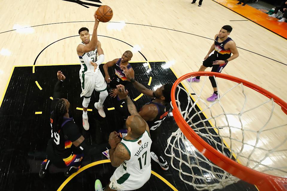 Giannis Antetokounmpo makes a leaping pass over Chris Paul during Game 1 of the NBA Finals.