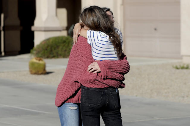 Madelyn Staddon, right, a relative of some of the members of a Mormon community who were attacked while traveling near the US-Mexico border, embraces a neighbor outside her home, Tuesday, Nov. 5, 2019, in Queen Creek, Ariz. Drug cartel gunmen ambushed three vehicles along a road near the state border of Chihuahua and Sonora on Monday, slaughtering at least six children and three women from the extended LeBaron family, all of them U.S. citizens living in northern Mexico, authorities said Tuesday. (AP Photo/Matt York)