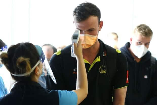 West Australian cricket player Ashton Turner has his temperature checked prior to G2G verification by West Australian police after arriving from Adelaide on Qantas flight QF889 at Perth Airport on November 14, 2020 in Perth, Australia.