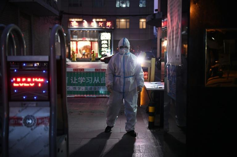 A Chinese security guard wears protective clothing outside a restaurant in Beijing -- the new coronavirus epidemic in China appears to be slowing