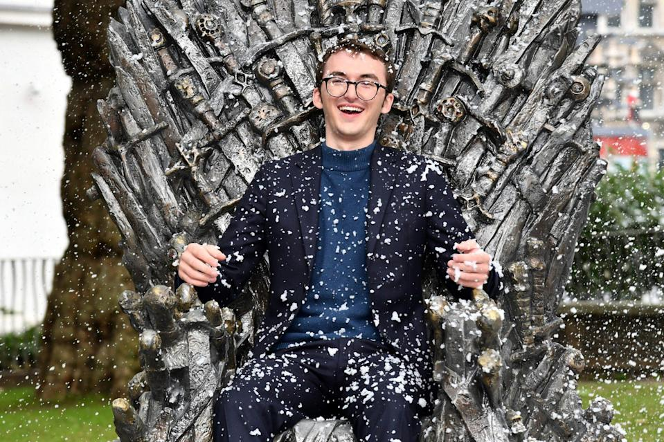 <p>Isaac Hempstead Wright takes his seat on the throne during the <em>Games of Thrones</em> Iron Throne unveiling, celebrating the 10-year anniversary of the show, on June 22 in Leicester Square, London.</p>