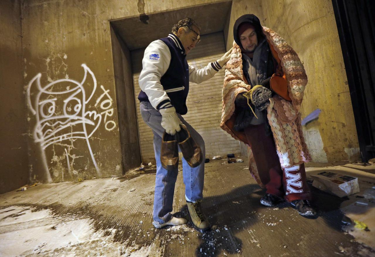 Doctor Patrick Angelo hands over the shoes off his feet to help a homeless man under the overpasses on Lower Wacker Drive in Chicago, Illinois, January 7, 2014. Angelo visits the homeless several times a week to hand out food, clothing and blankets to those living on the streets with the funding coming from his oral surgery medical practice and profits from his healthcare company. Angelo is in his 13th year doing charity work. Picture taken January 7, 2014. REUTERS/Jim Young (UNITED STATES - Tags: SOCIETY POVERTY TPX IMAGES OF THE DAY)