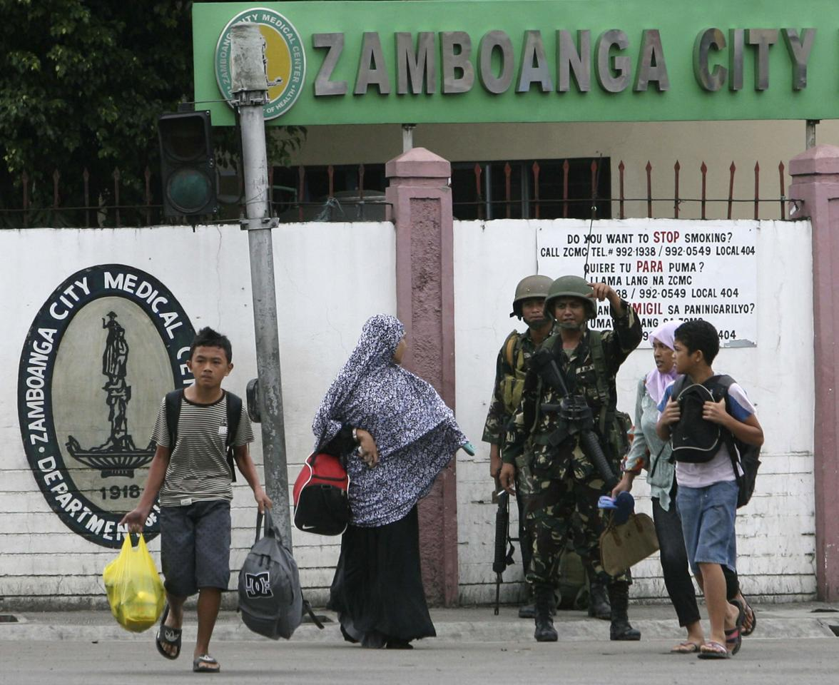 A government soldier directs civilian evacuees near an area where Muslim rebels members of the Moro National Liberation Front (MNLF) is occupying villages in Zamboanga City, southern Philippines September 9, 2013. Muslim rebels took 30 civilian hostages in the southern Philippines on Monday and held security forces in a standoff as part of a drive to derail peace talks, officials said. Police commandos cordoned off parts of Zamboanga City on the island of Mindanao after a rogue faction of the MNLF took hostages and tried to march to the city hall to raise their flag, an army commander said. REUTERS/STRINGER (PHILIPPINES - Tags: POLITICS MILITARY CIVIL UNREST)