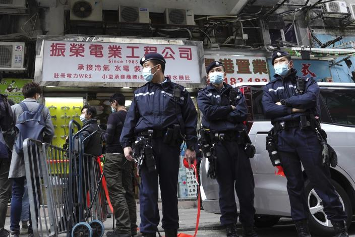 Police officers stand guard outside office of District councillor and lawyer Daniel Wong Kwok-tung, while police search in Hong Kong, Thursday, Jan. 14, 2021. Wong, a member of the city's Democratic Party, is known for providing legal assistance to hundreds of protesters arrested during the anti-government protests in Hong Kong in 2019. Hong Kong national security police on Thursday arrested a lawyer and 10 others on suspicion of helping 12 Hong Kongers try to flee the city, local media reported in the latest arrests in an ongoing crackdown on dissent. (AP Photo/Vincent Yu)