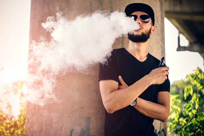 A young man with a beard blowing vape smoke from his mouth while outside.