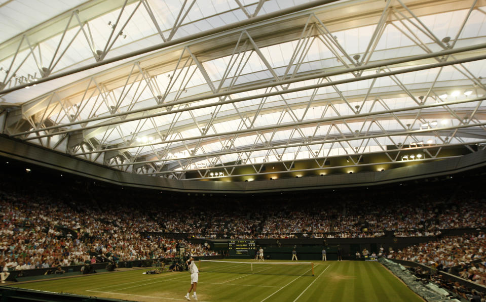 FILE - Stanislas Wawrinka, of Switzerland, foreground, serves to Andy Murray, of Britain, during their fourth round singles match at Wimbledon, in this Monday, June 29, 2009, file photo. How much do you know about Wimbledon? (AP Photo/Alastair Grant, File)