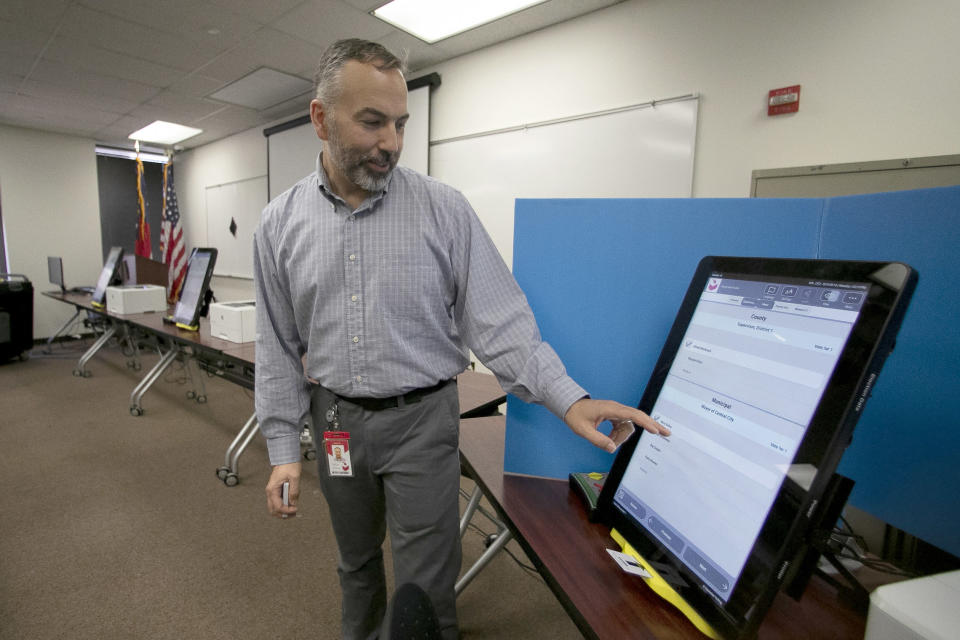 FILE- In this Sept. 16, 2019 file photo, Scott Tucker demonstrates the Dominion Voting system Georgia will use in Atlanta. Republican efforts to question the results of the 2020 election have led to two significant breaches of voting software that have alarmed election security experts who say they have increased the risk to elections in jurisdictions that use the equipment. (AP Photo/John Bazemore, File)