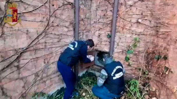 PHOTO: This image taken from a video distributed Wednesday, Dec. 11, 2019 by Italian police shows two forensic police officers approaching a metal panel in which a painting was found, in Piacenza, northern Italy. (Italian Police via AP)