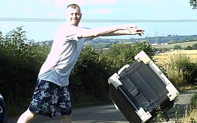 Fly-tipper caught smirking on camera as he dumped a washing machine at the side of a country lane - © SWNS.com