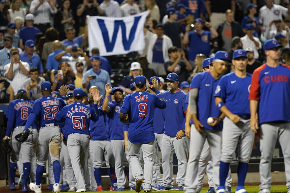 """Chicago Cubs fans hold a giant """"W"""" sign over the Chicago Cubs as they leave the field while Cubs manager David Ross, center left, and others greet Cubs shortstop Javier Baez (9) after the team defeated the New York Mets in a baseball game, Thursday, June 17, 2021, in New York. (AP Photo/Kathy Willens)"""