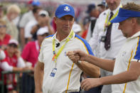 Team Europe captain Padraig Harrington talks to Team Europe's Ian Poulter on the 15th hole during a Ryder Cup singles match at the Whistling Straits Golf Course Sunday, Sept. 26, 2021, in Sheboygan, Wis. (AP Photo/Charlie Neibergall)