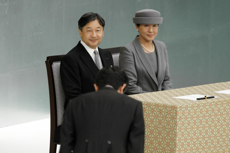 FILE - In this Aug. 15, 2019, file photo, Japanese Emperor Naruhito, and Empress Masako, look at Japanese Prime Minister Shinzo Abe bowing during a memorial ceremony for the war dead at Nippon Budokan Martial Arts Hall in Tokyo. (AP Photo/Eugene Hoshiko, File)